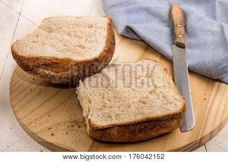 sliced northern irish breakfast bap on a round wooden board with bread knife