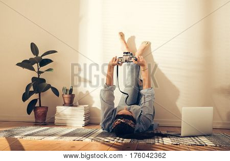 Female Photographer Lying On Her Back On The Floor