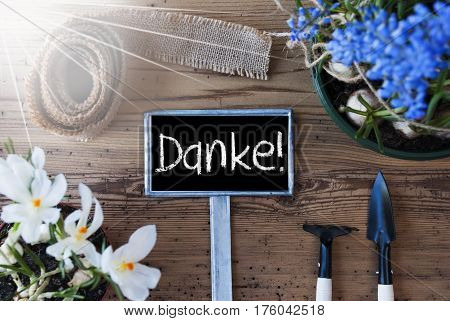 Sign With German Text Danke Means Thank You. Sunny Spring Flowers Like Grape Hyacinth And Crocus. Gardening Tools Like Rake And Shovel. Hemp Fabric Ribbon. Aged Wooden Background