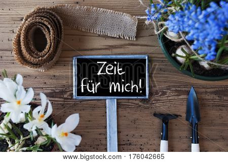 Sign With German Text Zeit Fuer Mich Means Time For Me. Spring Flowers Like Grape Hyacinth And Crocus. Gardening Tools Like Rake And Shovel. Hemp Fabric Ribbon. Aged Wooden Background