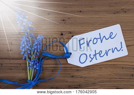 Label With German Text Frohe Ostern Means Happy Easter. Sunny Blue Spring Grape Hyacinth With Ribbon. Aged, Rustic Wodden Background. Greeting Card For Spring Season