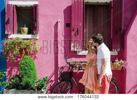 Tender young couple with a bicycle near a funny purple house in Burano island Venice Italy