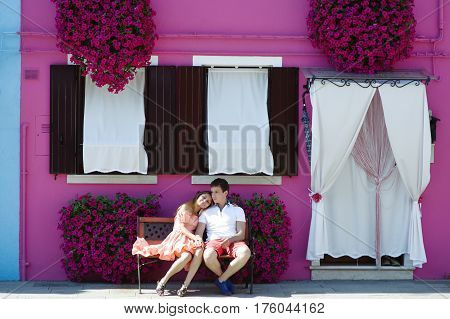 Young travel couple on vacation relaxing on a bench near a purple house in Burano Venice Italy