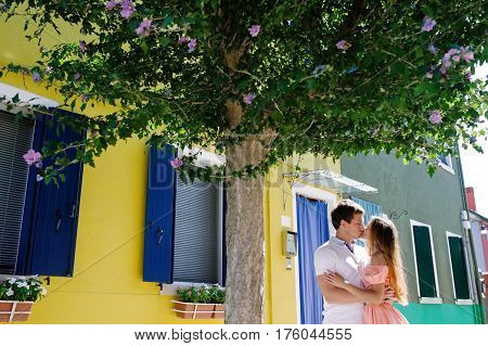 Young couple embracing and kissing under a tree in Burano island Venice Italy