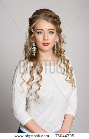 Beautiful girl with a fashionable hairdress with curls on a gray background