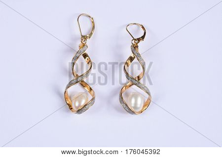 Gold and diamond twisted earrings with a large pearl inside against a white background UK.