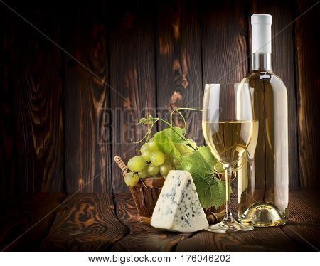 White wine with grapes and blue cheese on a wooden background