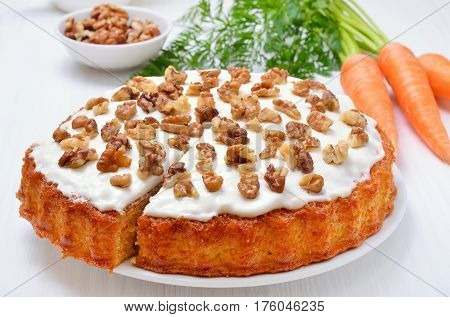 Homemade carrot cake and fresh carrots on white table close up view
