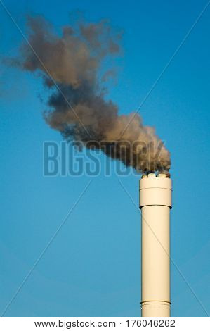 Smoke coming from a chimney rising against a clear nice blue sky