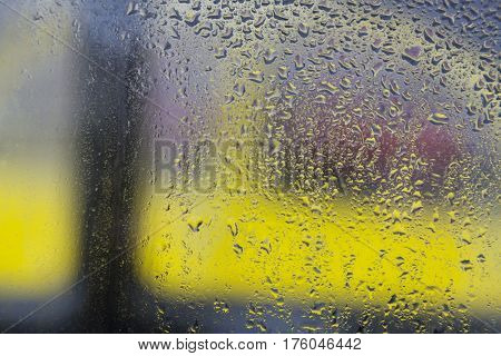 rain drops on windshield of car and background in shades of yellow and red