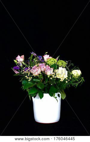Bouquet of flowers in a white vase against a black background UK.