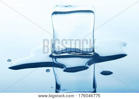One melting ice cube with reflection isolated on white background. Closeup of cold crystal block cutout