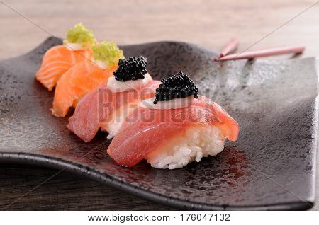 Tuna and salmon sushi set with caviar and chopsticks