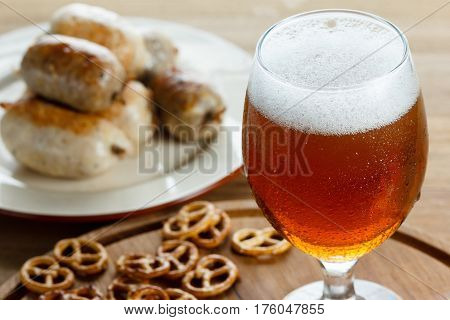 A glass of cold foamy beer with pretzels and grilled sausages. Traditional german Oktoberfest snacks and beer