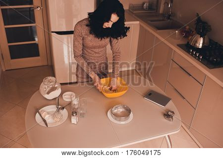 Brunette woman kneading dough in kitchen. Making cake. Top view.