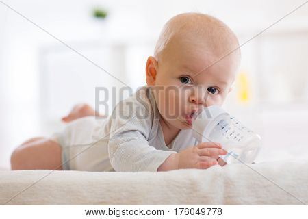 Baby lying on belly and drinking water from a bottle