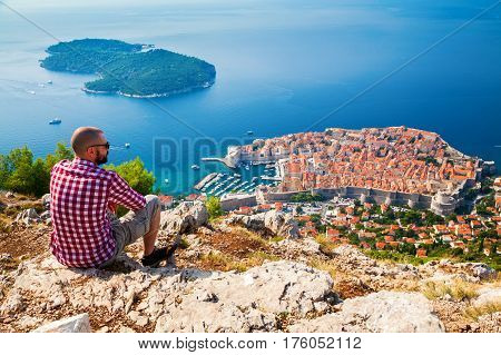 tourist man looking down to the Old Town of Dubrovnik sitting on the mountain above the city Croatia