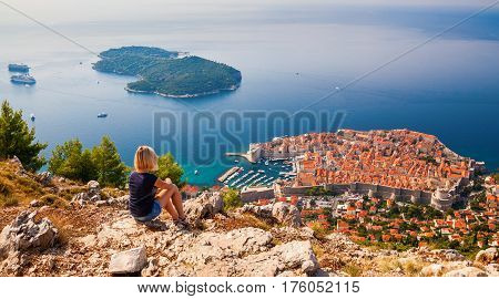 young woman enjoying the view of the Dubrovnik Old Town sitting on the mountain above the city Croatia
