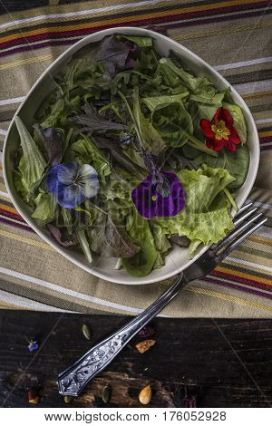 Spring green salad with edible flowers over a dark table