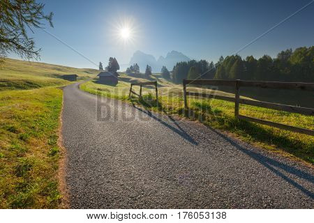 Driving on idyllic mountain road at beautiful morning. Landscape on Alpe di Siusi or Seiser Alm at Dolomites Italy.