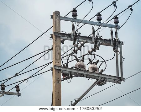 Electric pole with electric transformers and electrical cables on a  sky background