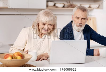 Getting familiar with modern gadgets. Pleasant smiling involved aged couple sitting at home and using laptop while expressing interest and joy