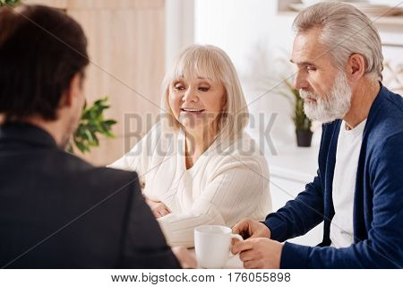 Making a real estate purchase. Optimistic happy elderly couple sitting at home and having conversation with advisor while expressing interest