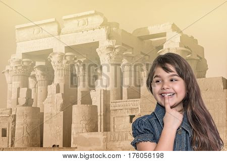 Smiling long haired tanned little girl with her finger over her mouth is standing in front of Kom Ombo temple in Egypt. Landmark in the background is edited as a vintage photo in sunlight.