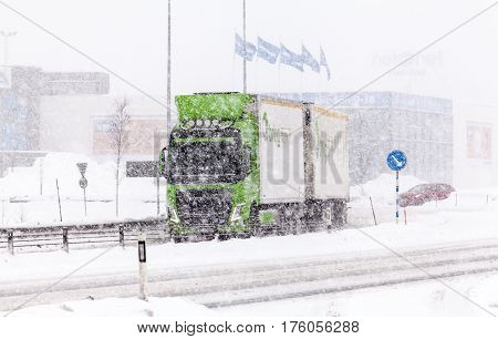 UMEA, SWEDEN ON MARCH 02. View of a modern highway, the traffic, truck in snowy condition on March 02, 2017 in Umea, Sweden. Buildings in the background. Editorial use.