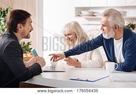 Helping to make a decision. Skilled confident professional finance advisor having conversation with elderly customers and using laptop while expressing positivity