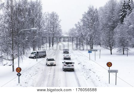 UMEA, SWEDEN ON MARCH 02. View of a modern street, road and the traffic in snowy condition on March 02, 2017 in Umea, Sweden. Signs and buildings. Editorial use.