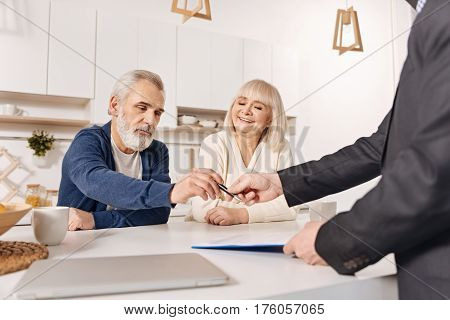 Full of determination. Decisive cheerful aged couple sitting at home and having conversation with social security advisor while signing the agreement