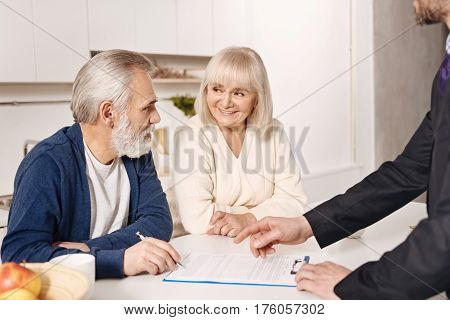 Making crucial decision. Optimistic cheerful sincere senior couple sitting at home and having meeting with real estate agent while signing the agreement
