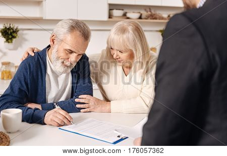 Signing our loan contract. Smiling charming merry elderly couple sitting at home and having meeting with real estate agent while signing documents