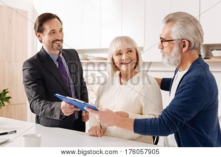 Considering plan of the deal. Smart confident upbeat lawyer meeting with old couple of clients while working and giving professional consultation about buying house