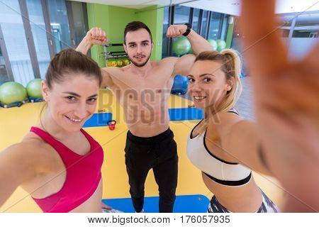 Group of sportive people in a gym taking selfie - Happy sporty friends in a weight room while training - Concepts about lifestyle and sport in a fitness club.