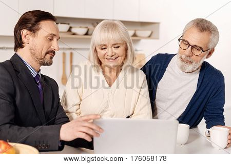 Persuading in a beneficial choice. Optimistic confident skilled real estate agent meeting with aged couple of customers while presenting the plan of the house and using laptop