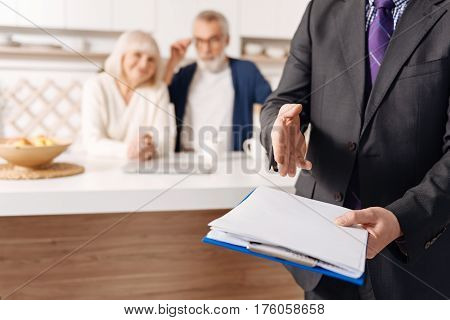 Take care about your health beforehand. Confident experienced skillful social security agent working and presenting contract while senior couple of clients sitting in the background
