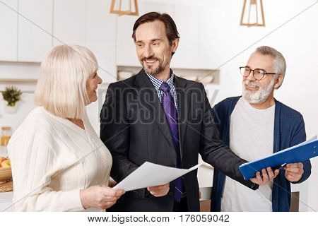 Helping people in legal questions. Experienced proficient positive legal advisor having meeting and presenting contract to the elderly couple of clients while expressing happiness