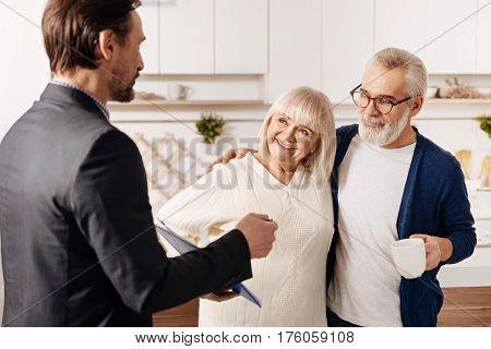 Improving life of our senior generation. Proficient smart helpful legal advisor having meeting and presenting contract to the aged couple of clients while expressing confidence