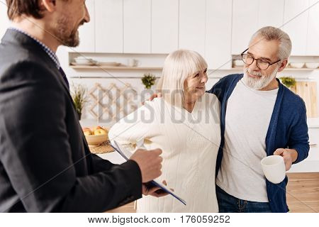 Helping our aged generation. Proficient delighted smiling legal advisor having meeting and presenting agreement to the aged couple of clients while expressing positivity