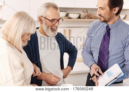 Choosing variants of investment. Qualified positive upbeat realtor talking to aging couple of clients while presenting the contract for apartment investment and expressing joy