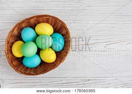 Colored eggs in basket. Top view. Concept Happy Easter.