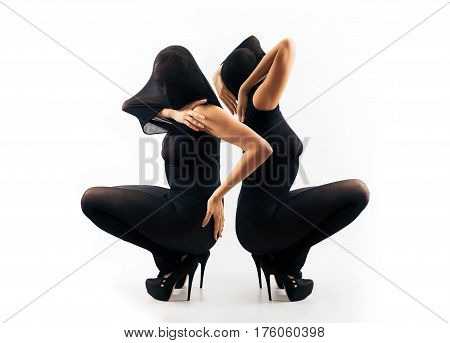 Part of series. Two female silhouettes in black nylon body stocking and in high heels shoes interacting with each other horizontal view. Double portrait from two different side views.
