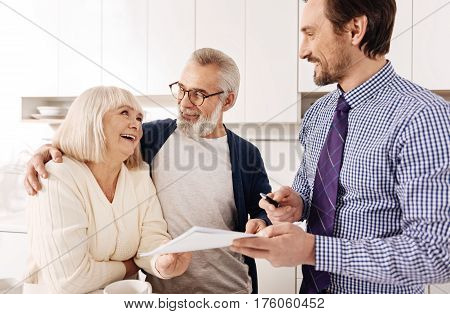 Consulting with professional. Friendly optimistic harmonious senior couple meeting with financial adviser and consult with him while choosing the variant for investment