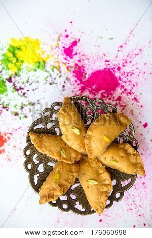 Gujhia- a North Indian traditional festive sweet dish. Khoya stuffed fried dumplings arranged on a decorative plate against splashed powder colors on the occasion of Holi festival.