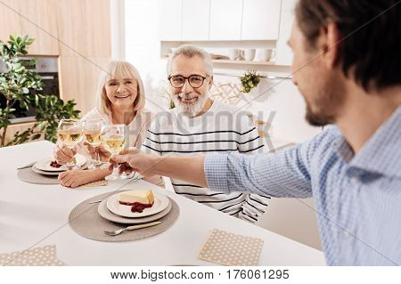 Raising the glass for my parents. Charismatic delighted handsome man having dinner and enjoying holiday with his elderly parents while raising glasses full of champagne and greeting