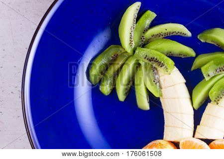 Fruit salad in form of tropical plams on blue plate close up