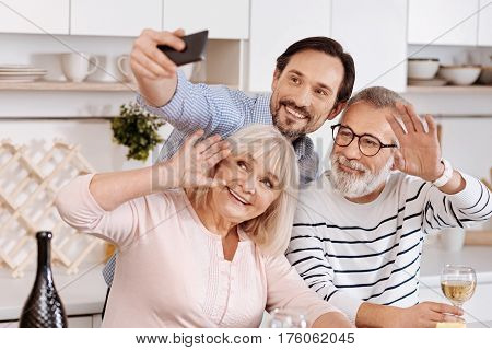 Full of joy. Happy young smiling man having dinner and enjoying free time with his aged parents while holding the mobile and making selfie