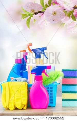 Spring cleaning concept - colorful spays and rubbers on wooden table over spring background
